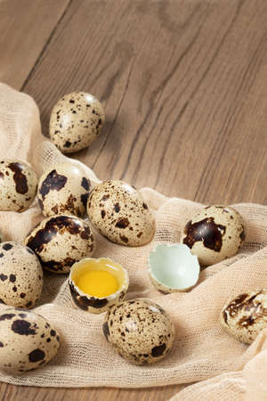 Composition of several quail eggs on decorative fabric on a wooden table close-up, copy space, virtical banner, flatlay
