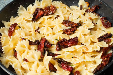 Pan-fried pasta with sun-dried tomatoes and garlic. Stages of cooking Italian cuisine