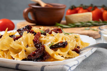 Pasta with sun-dried tomatoes and parmesan in a white plate on the table. Italian cuisine, ingredients and the finished dish