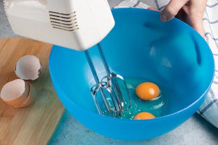 Whisking fresh chicken eggs in a blue bowl Stok Fotoğraf