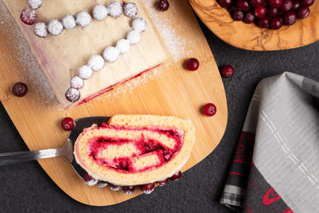 Homemade biscuit sweet roll with cranberries and cream on a black table, top view, flat lay