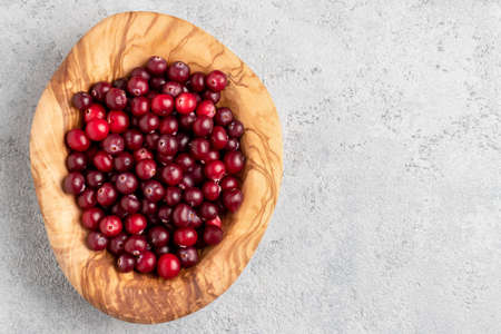 Ripe fresh cranberries in a wooden bowl on a gray table, copy space, top view, flat lay