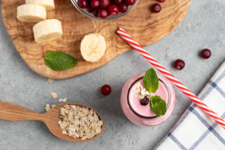 Homemade yogurt smoothie with banana, cranberry and oatmeal, top view, flat lay