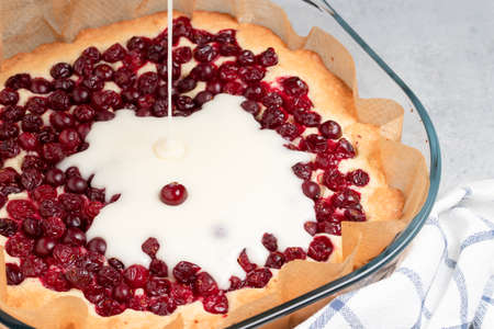 Homemade baking. Cooking sweet cranberry pie. Pouring cream