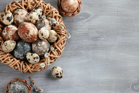 Easter composition - several marble eggs painted with natural dyes in a wicker nest and baskets, top veiw 免版税图像