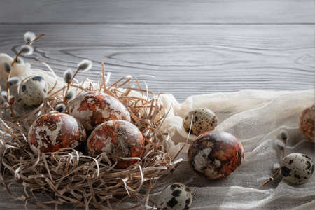 Easter composition - several marble eggs painted with natural dyes in a paper nest on the table, copy space