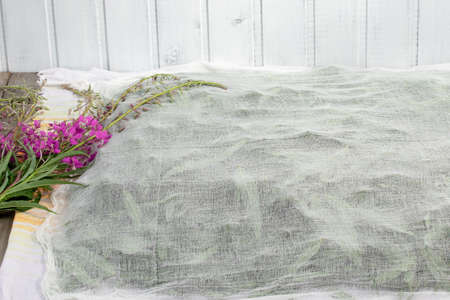 Harvesting fireweed for tea - drying spread leaves and flowers under a thin cloth