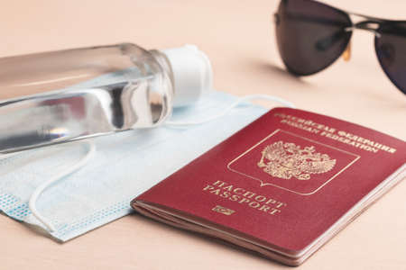 Safe travel during  pandemic concept. Protective medical mask, sunglasses, sanitizer and Russian passport on the table