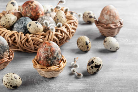 Easter composition - several marble eggs painted with natural dyes in a wicker nest and baskets
