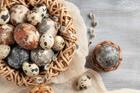 Easter composition - several marble eggs painted with natural dyes in a wicker nest and baskets, top veiw Banque d'images