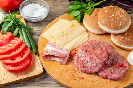 Process of cooking homemade burgers, meatballs, tomatoes, cheese and other ingredients on a wooden table, flat lay, top view