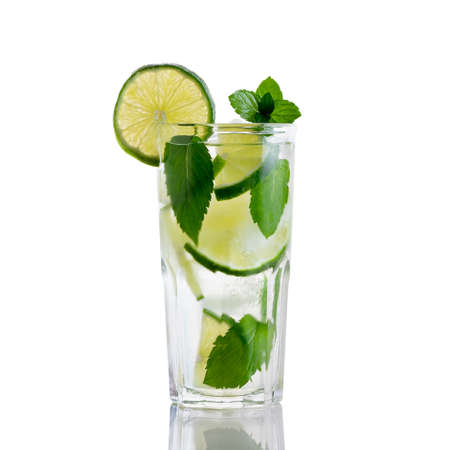 Fresh homemade mojito cocktail in a tall glass with lime, mint and ice isolated on white background