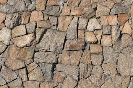 Stone wall of granite close-up, texture, background.