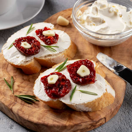 Homemade sandwiches with cream cheese and sun-dried tomatoes on a wooden board of olive - delicious healthy breakfast, italian cuisine, square image.