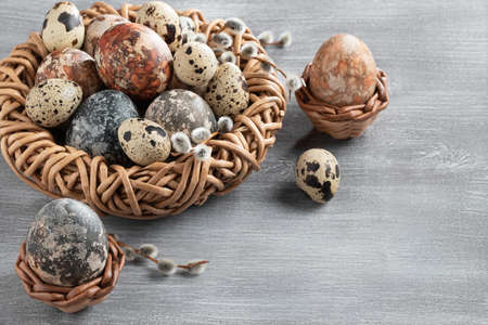 Easter composition - several marble eggs painted with natural dyes in a wicker nest and baskets, top view, copy space. Banque d'images