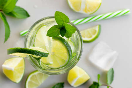 Fresh homemade cocktail with lime, mint and ice on a white table, close up, top view. Banque d'images
