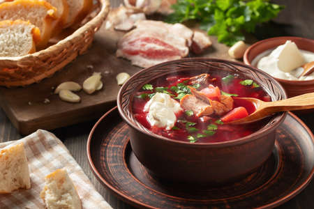 Freshly cooked hot homemade borscht - traditional dish of Russian and Ukrainian cuisine in earthenware dishes with bacon, bread, sour cream and garlic