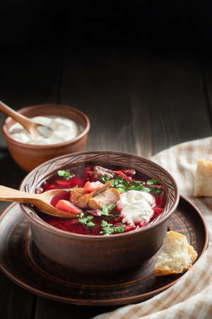 Freshly cooked borscht - traditional dish of Russian and Ukrainian cuisine in earthenware dish with bacon, sour cream and garlic, vertical image Banque d'images