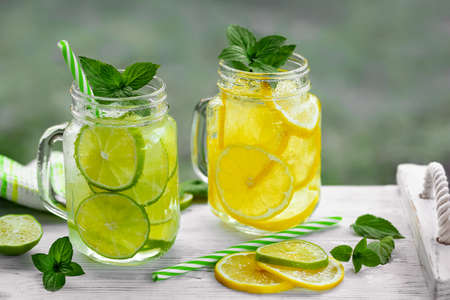 Cold refreshing homemade lemonade with mint, lemon and lime in mason jars