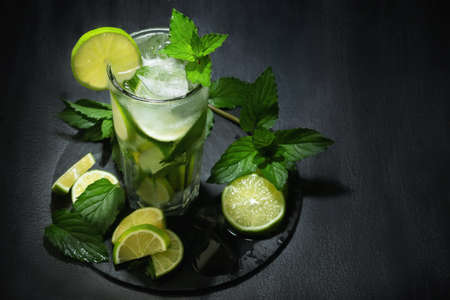 Fresh homemade mojito cocktail in a tall glass with lime, mint and ice on a black table, copy space