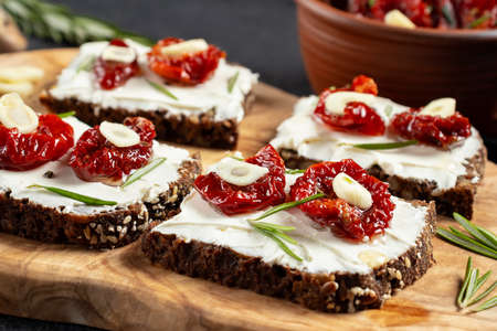 Homemade multigrain bread sandwiches with cream cheese and sun-dried tomatoes on a wooden platter, close-up. Healthy eating concept Banque d'images