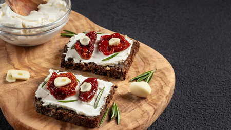 Homemade multigrain bread sandwiches with cream cheese and sun-dried tomatoes on a wooden platter. Healthy eating concept, copy space