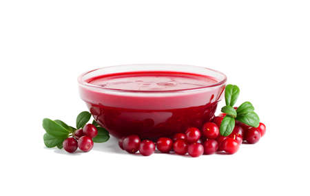 Homemade fresh wild lingonberry sauce in small glass bowl isolated on white background