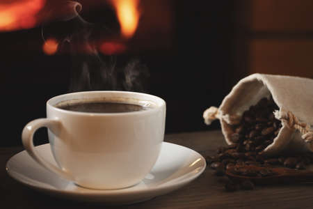 Close-up of cup of hot coffee and coffee beans in a bag on a wooden table in front of a burning fireplace. Selective focus Banque d'images