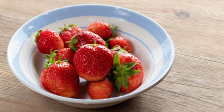 Natural ripe strawberries in a plain white bowl on a wooden table