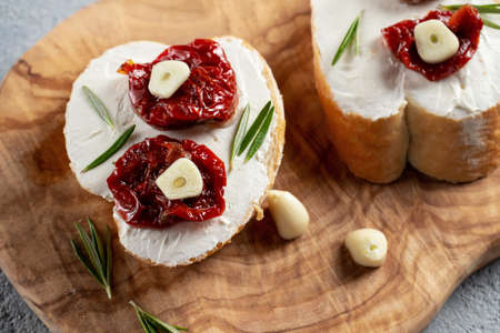 Homemade sandwiches with cream cheese and sun-dried tomatoes on a wooden board of olive - delicious healthy breakfast, italian cuisine