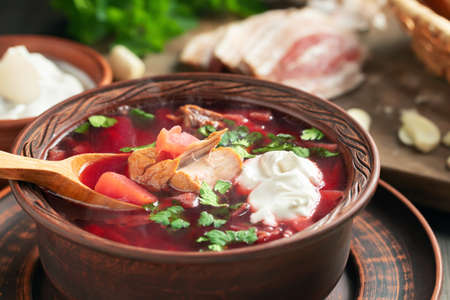 Freshly cooked borscht - traditional dish of Russian and Ukrainian cuisine in earthenware dishes with bacon, bread, sour cream and garlic, close up