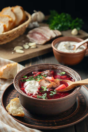 Freshly cooked borscht - traditional dish of Russian and Ukrainian cuisine in earthenware dish with bacon, sour cream and garlic, vertical image 免版税图像