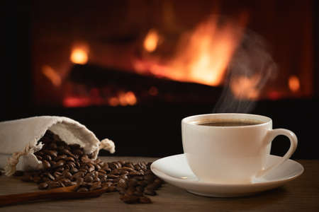 Cup of hot coffee and coffee beans in a bag on a wooden table in front of a burning fireplace. Selective focus 免版税图像