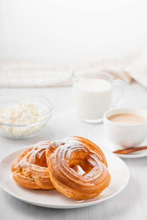 Morning coffee with cake. Custard rings, coffee, cream, cottage cheese on a white wooden table. Vertical image