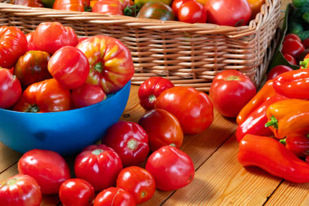 Fresh ripe natural tomatoes and peppers on a wooden table and in a bowl - farm harvest
