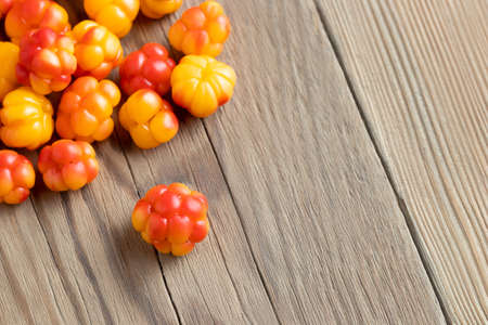Fresh ripe cloudberries on a wooden table close-up