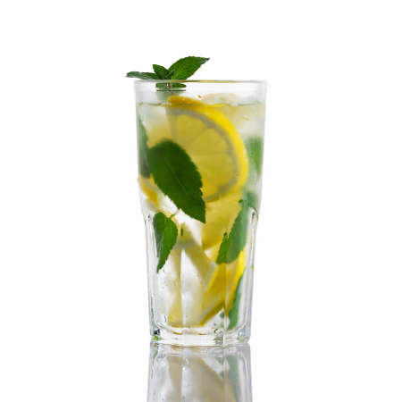 Fresh homemade cocktail in a tall glass with lemon, mint and ice isolated on white background