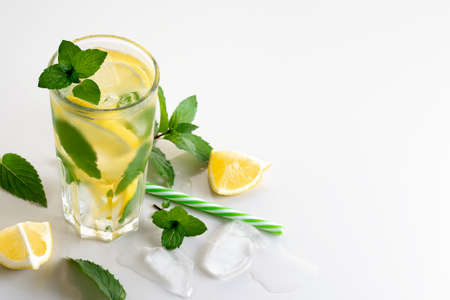 Fresh homemade cocktail with lemon, mint and ice on a white table, copy space