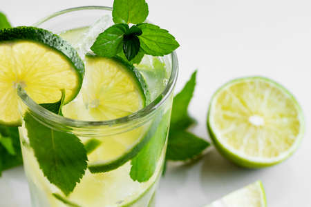 Fresh homemade cocktail with lime, mint and ice on a white table, close up