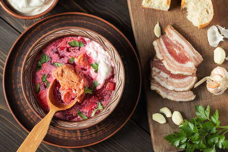 Freshly cooked borscht - traditional dish of Russian and Ukrainian cuisine in earthenware dishes with bacon, bread, sour cream and garlic, top view