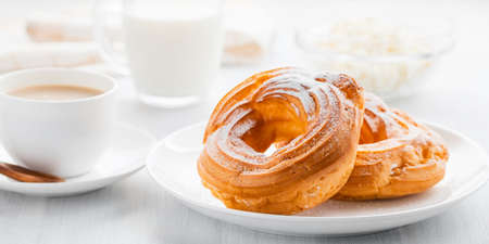 Morning coffee with cake. Custard rings, coffee, cream, cottage cheese on a white wooden table