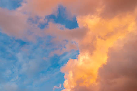 Beautiful cloudscape - pink-orange clouds in the rays of the sun against the blue sky