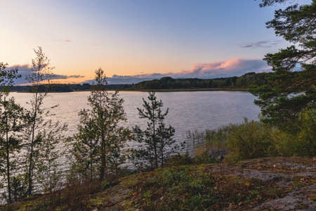 Sunset on a lake with rocky shores in Karelia
