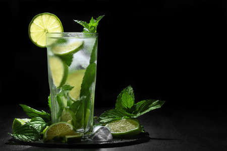 Fresh homemade mojito cocktail in a tall glass with lime, mint and ice on a black background, copy space 免版税图像