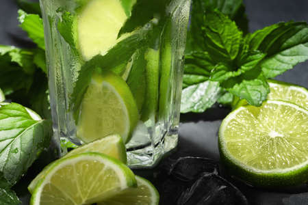Fresh homemade mojito cocktail with lime, mint and ice on a black background, close-up