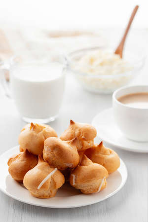 Morning coffee with cakes. Profiteroles, coffee, cream, cottage cheese on a white wooden table. Vertical image