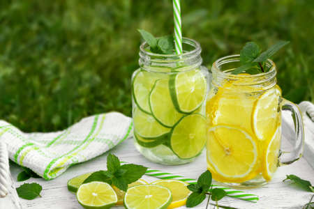 Cold refreshing homemade lemonade with mint, lemon and lime in mason jars on a summer lawn, copyspace