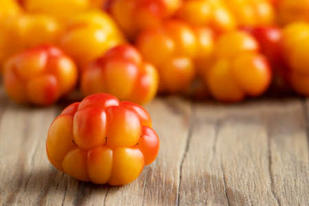 Fresh ripe cloudberries on a wooden table close-up. Selective focus