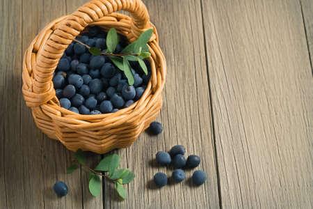 Wild forest blueberries in a small basket on a wooden table