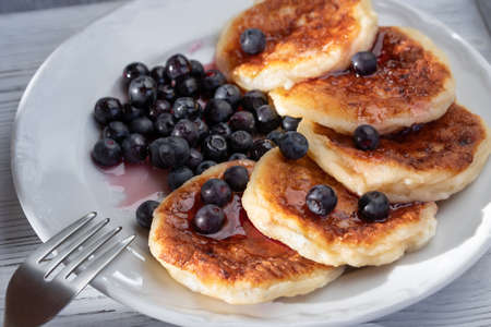 Fresh cottage pancakes with cheese and blueberries in syrup. Summer breakfast in the village